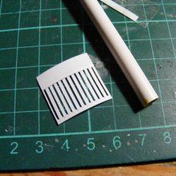 Die Textur des Munitionscontainers wurde mit 0,25mm PlaPlate umgesetzt, in das ein Rillenmuster geschniten wurde. Danach wurde das Stück um das Rohr gelegt. Hierbei hilft es, das bauteil kurz in warmes Wasser zu legen.